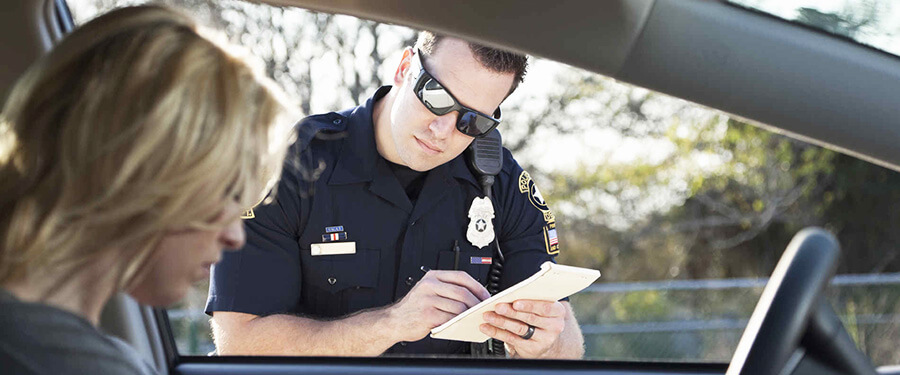 Police officer writing ticket to woman